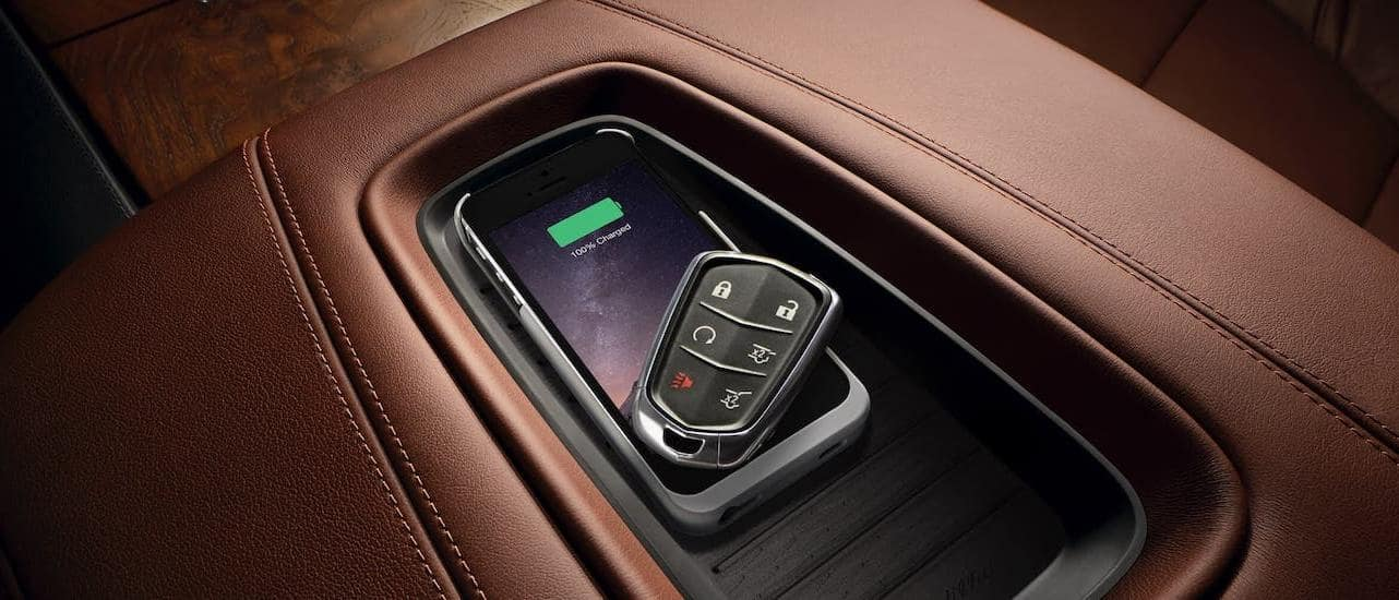 A phone and key fob are shown in the wireless charging pad in a 2020 Cadillac Escalade with brown leather interior. This is some of the technology that helps the Escalade win in the 2020 Cadillac Escalade vs 2020 Chevy Suburban comparison.