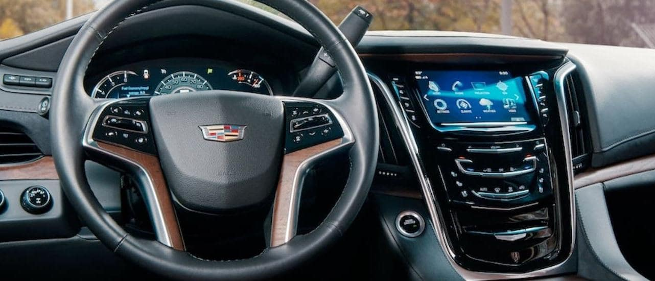 The steering wheel and infotainment center are shown in a 2020 Cadillac Escalade.