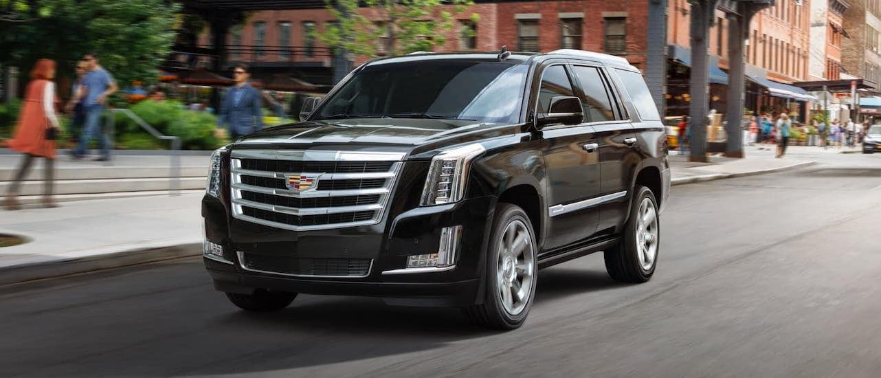 A black 2020 Cadillac Escalade is driving in downtown Fort Worth, TX.