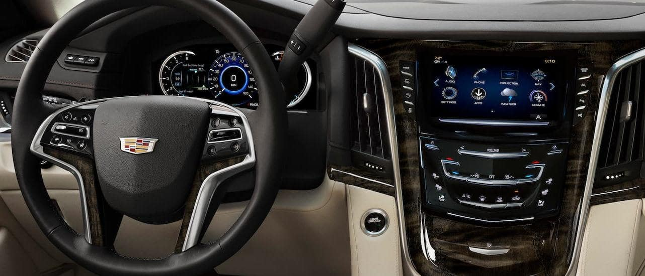 The tan, black and wood dashboard and steering wheel are shown in a 2020 Cadillac Escalade in Fort Worth, TX.