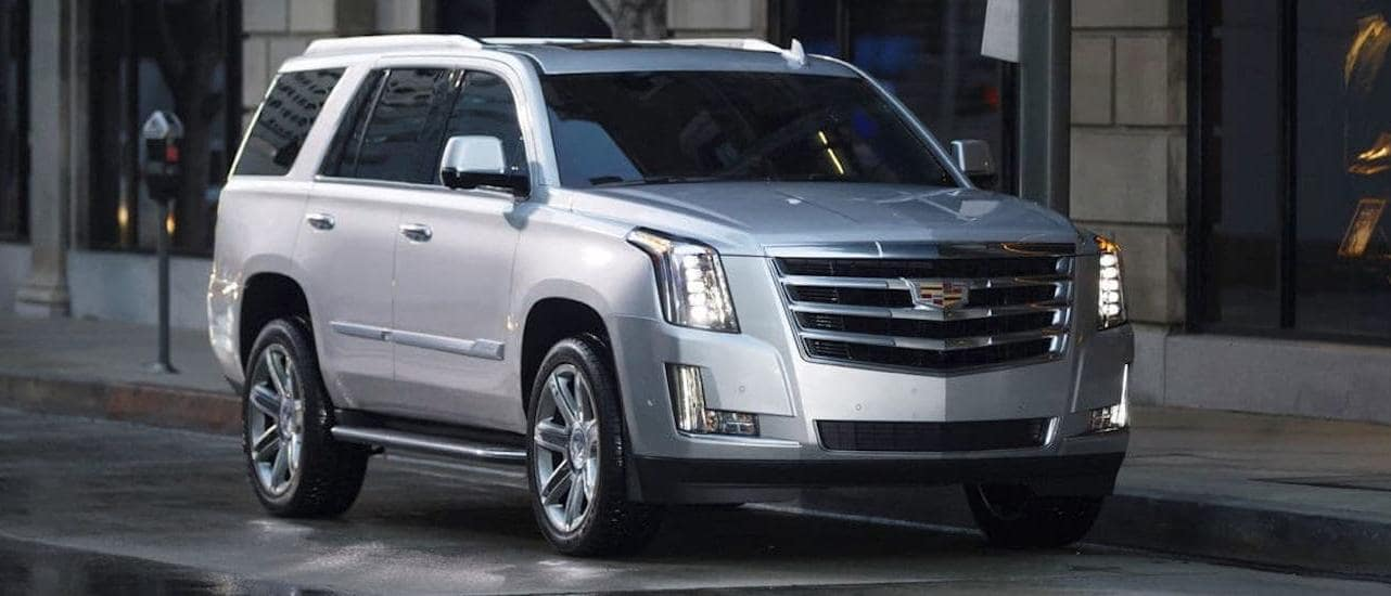 A silver 2020 Cadillac Escalade is parked on a city street after winning the 2020 Cadillac Escalade vs 2020 Lincoln Navigator comparison.
