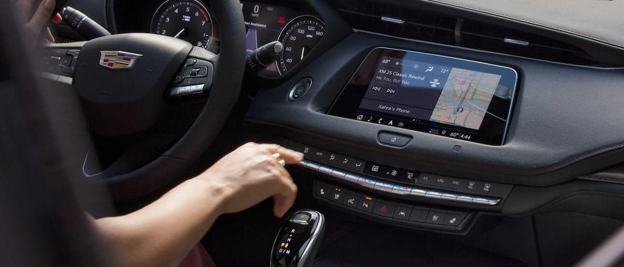 A driver is using the touchscreen inside the 2020 Cadillac XT4.