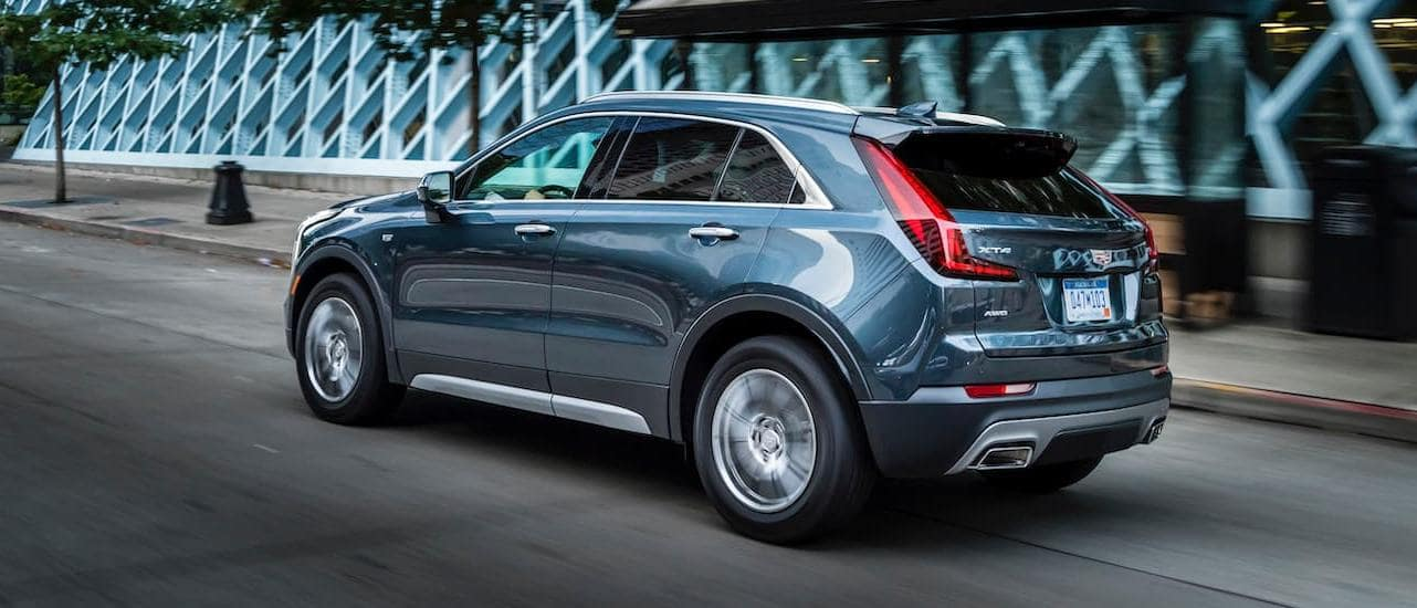 A blue 2020 Cadillac XT4, which wins when comparing the 2020 Cadillac XT4 vs 2020 BMW X1, is driving on a city street.