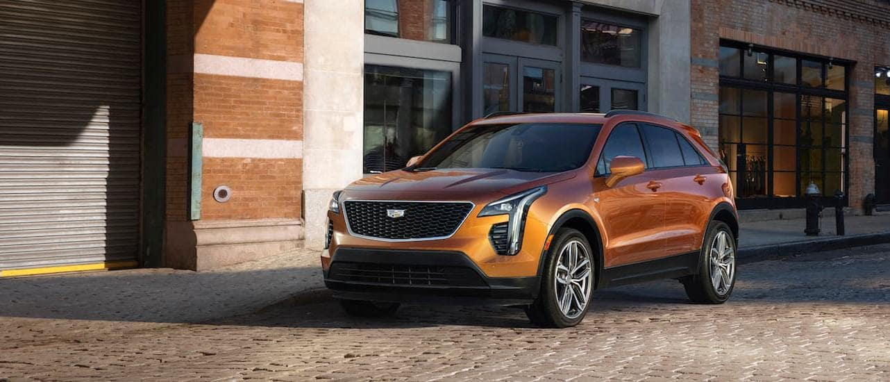 An orange 2020 Cadillac XT4 is parked in front of brick buildings near Fort Worth, TX.