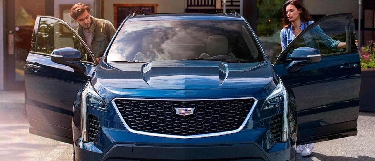 A couple is getting into a blue 2020 Cadillac XT4, shown from the front.
