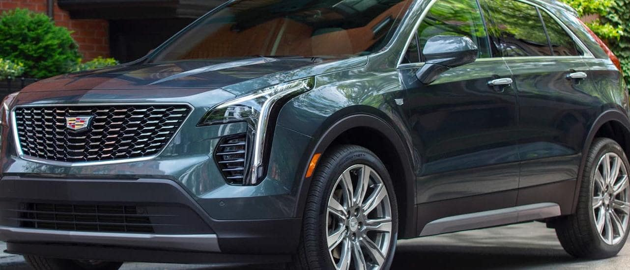 A gray 2020 Cadillac XT4 is parked in front of a Fort Worth, TX, building.