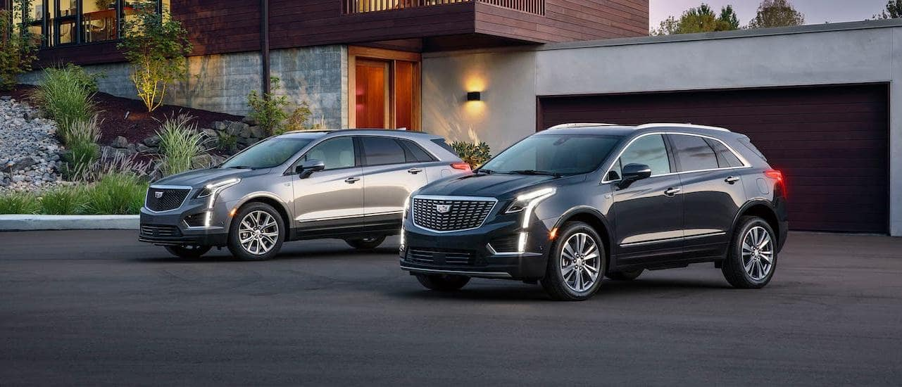 Two 2020 Cadillac XT5s are parked in a driveway outside Fort Worth, TX, one silver Sport and one black Premium Luxury.