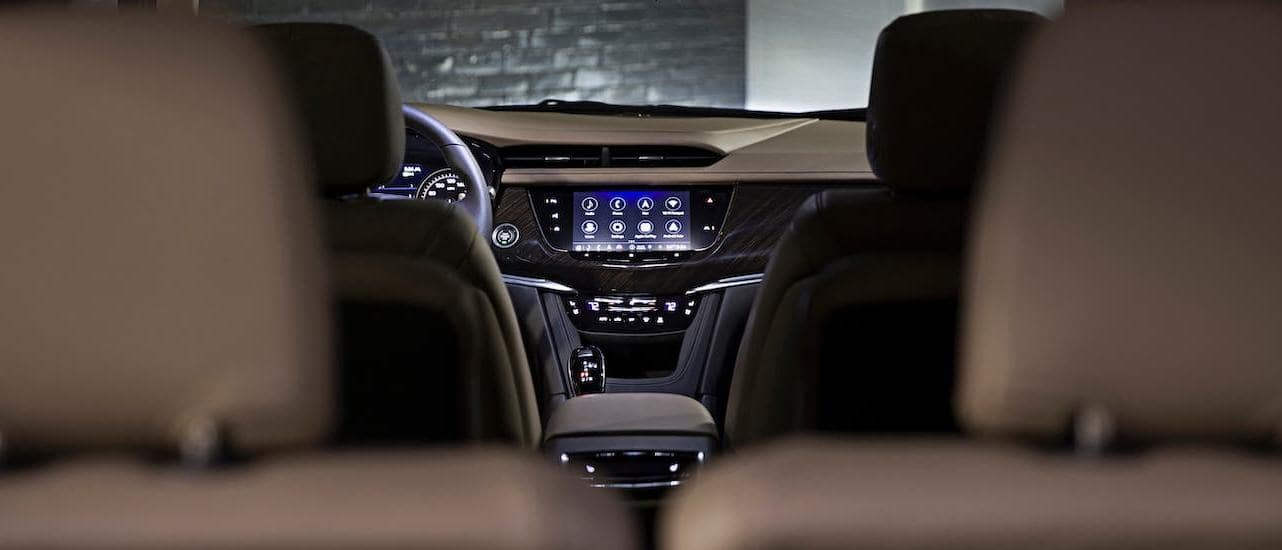The infotainment screen is shown from the view of the third row of seats in a 2020 Cadillac XT6, the winner of 2020 Cadillac XT6 vs 2020 Kia Telluride.