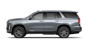 A blue/silver 2021 Cadillac Escalade is facing left against a white background.