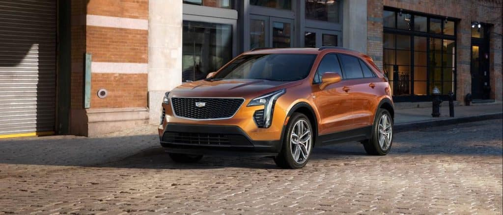 An orange 2020 Cadillac XT4, a popular Cadillac SUV model, is shown parked on a cobblestone street.