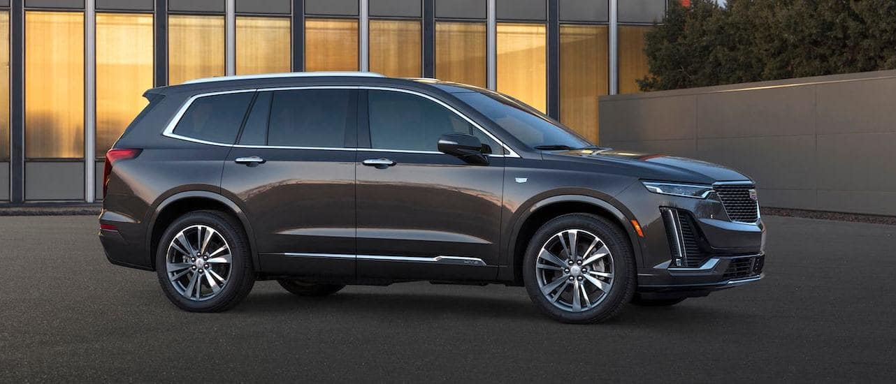 A gray 2020 Cadillac XT6 is parked in front of an office building near Fort Worth, TX.