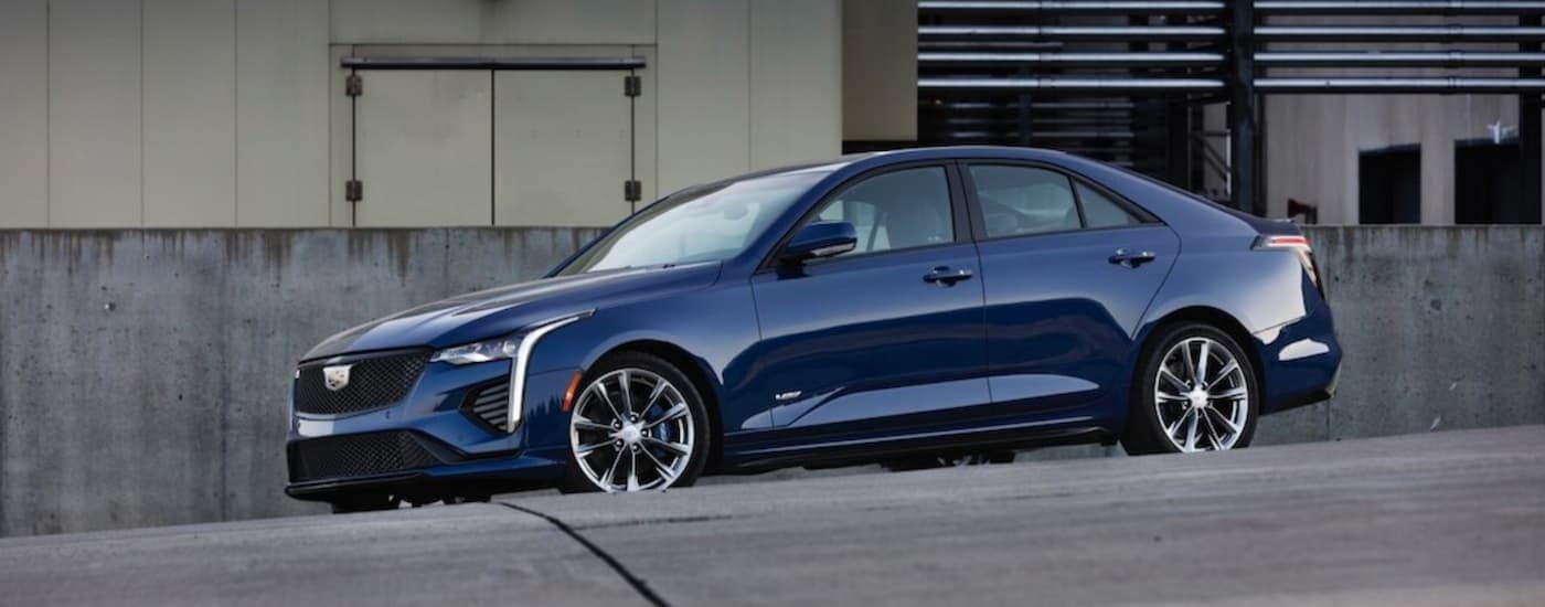 A blue 2020 Cadillac CT4 is parked in front of an industrial building after leaving a Cadillac dealer near me in Fort Worth, TX.