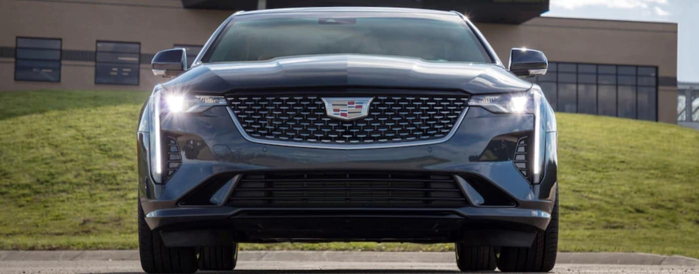 A dark grey 2020 Cadillac CT4 is facing forward in front of a Cadillac dealership in Fort Worth, TX.