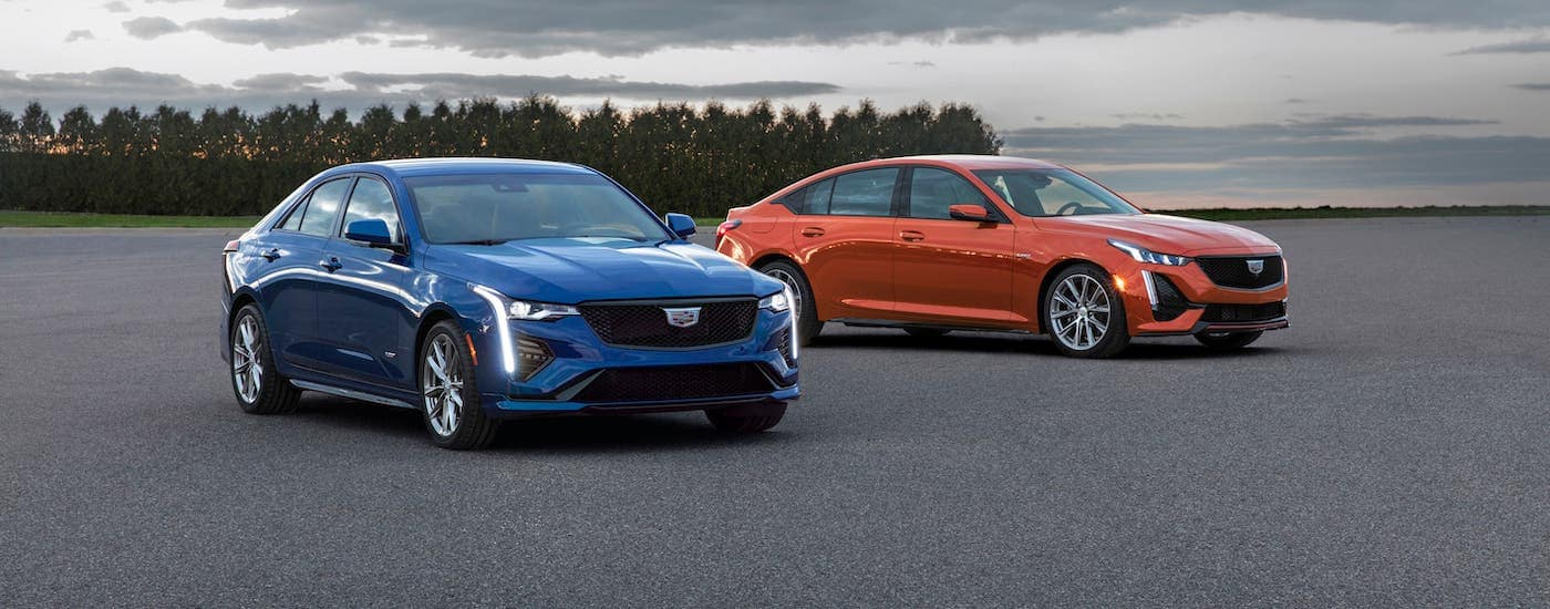A blue 2020 Cadillac CT4-V and an orange CT5-V from a local Cadillac dealership are parked in an open lot near Fort Worth, TX.