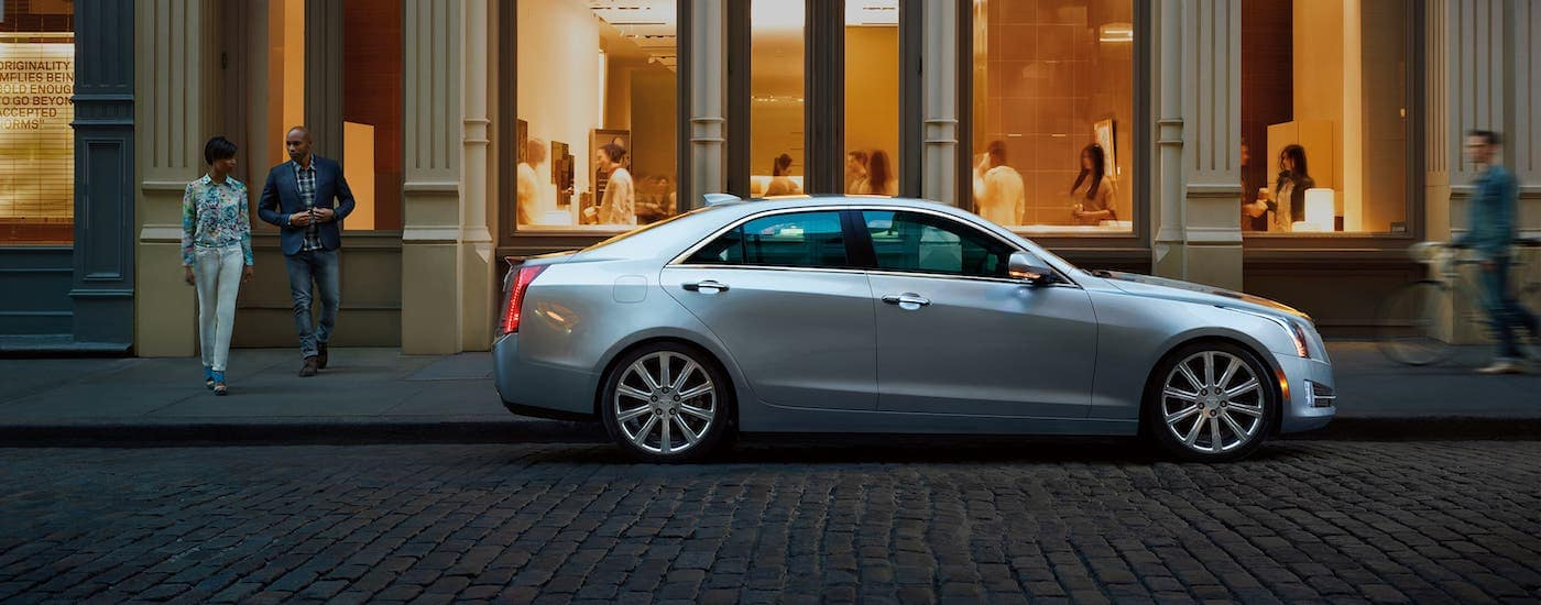 A silver 2014 Cadillac ATS is parked on a cobblestone road outside Fort Worth, TX.