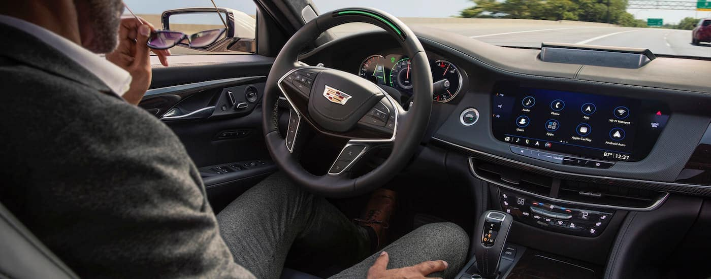 A man is driving one of the popular Cadillacs for sale with Super Cruise hands-free technology.