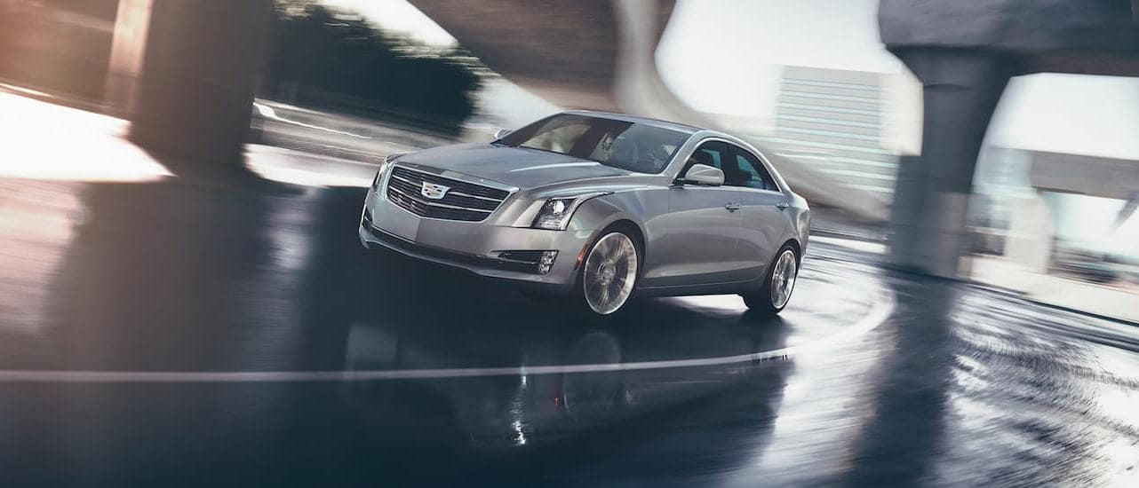A silver 2017 Cadillac ATS is driving under a highway overpass.