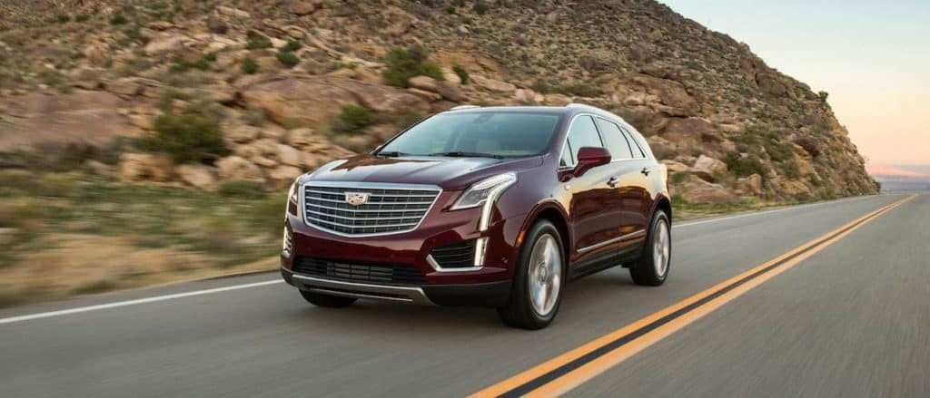 A burgundy 2018 pre owned Cadillac XT5 is driving on a desert road near Fort Worth, TX.