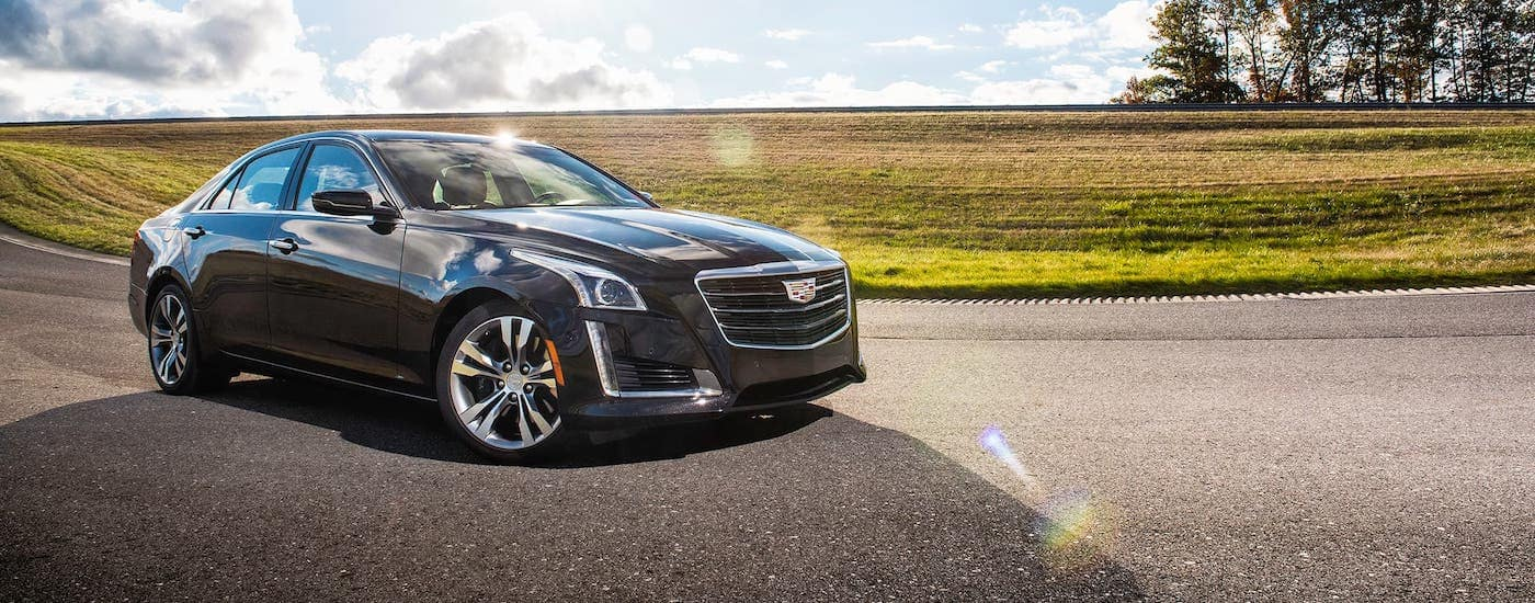 A black 2017 Cadillac CTS is parked in front of a Fort Worth, TX, field and blue sky.