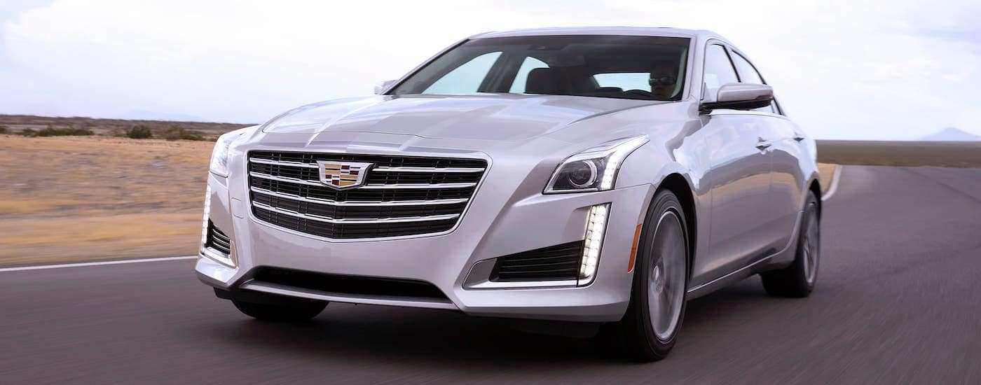 A white 2017 used Cadillac CTS sedan is driving on a highway near Fort Worth, TX.