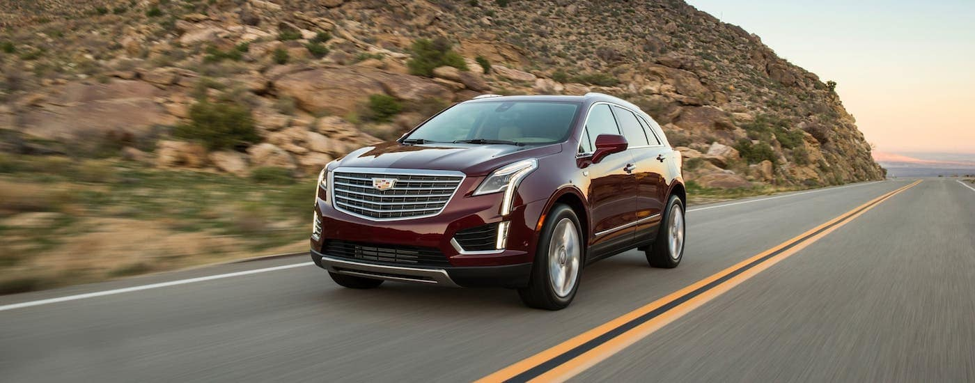 A burgundy 2017 Used Cadillac SUV XT5 driving by a rock-covered hill outside Fort Worth, TX.