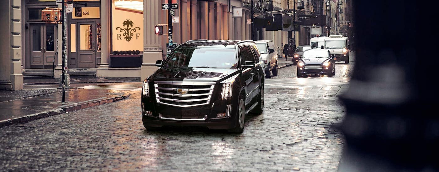 A black used Cadillac SUV, a 2017 Cadillac Escalade, is driving on a street near Fort Worth, TX, after the rain.