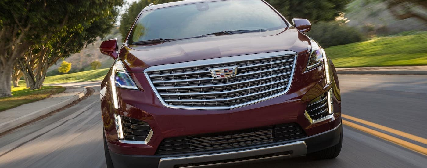 A great find for a used Cadillac for sale in Fort Worth, a red 2019 Cadillac XT5 Platinum, is shown driving on a highway from the front.