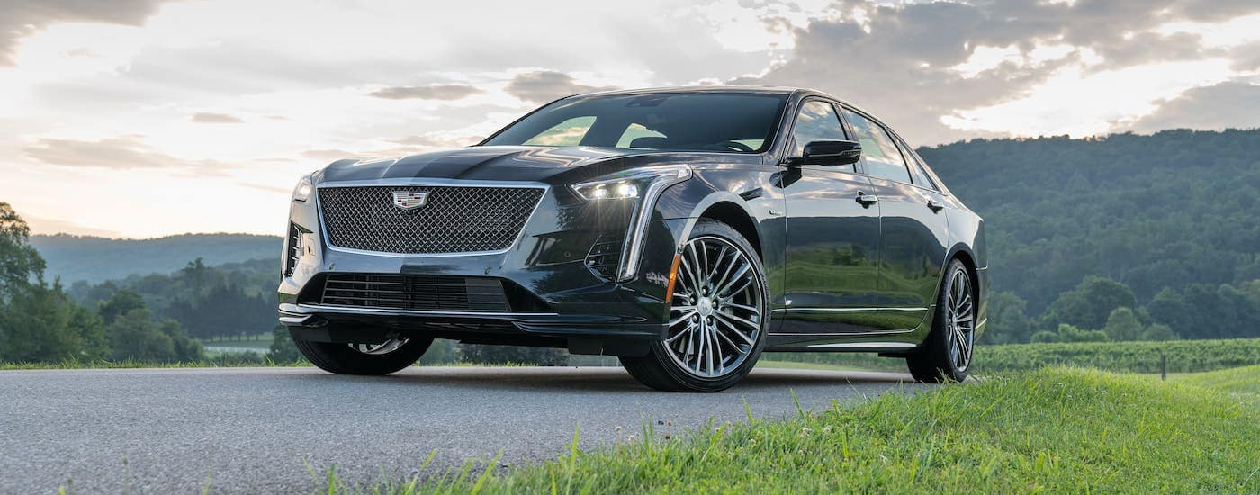 A dark gray 2019 Cadillac CT6-V used luxury car is parked in front of rolling hills at sunset. Visit your Fort Worth Cadillac dealer to see one today.