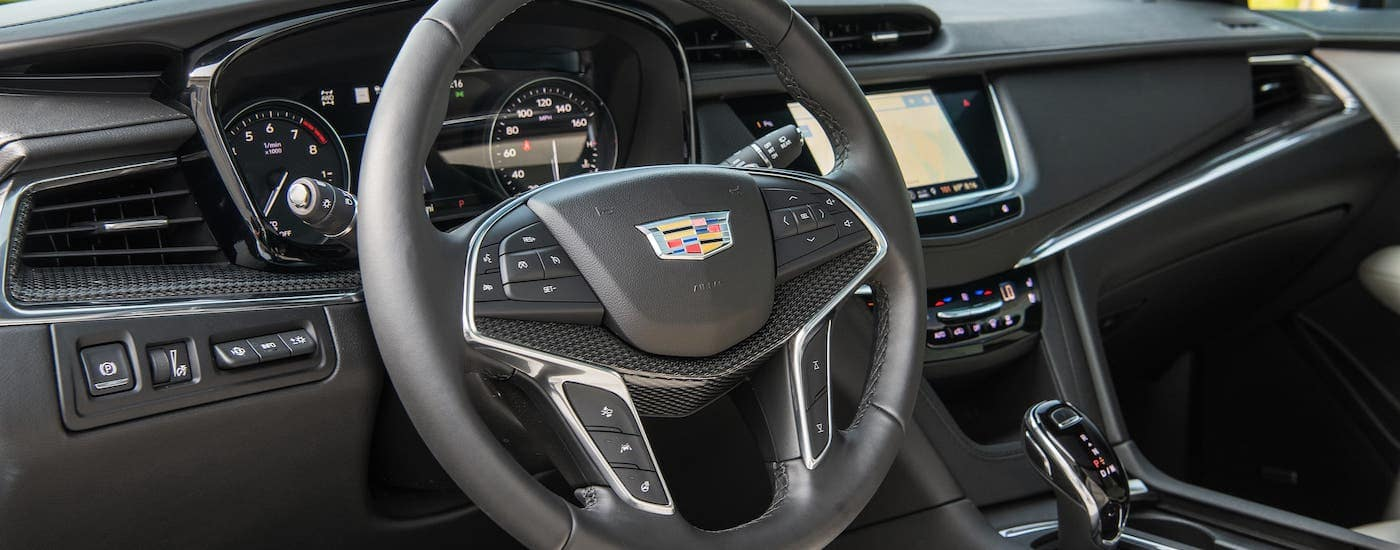 The black interior steering wheel and dashboard are shown in a 2020 Cadillac XT5.