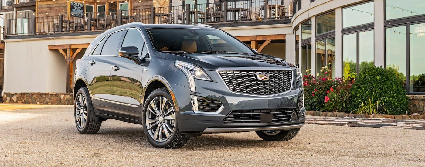 A gray 2020 Cadillac XT5 is parked in front of a vineyard after winning the 2020 Cadillac XT5 vs 2020 Audi Q5 comparison.