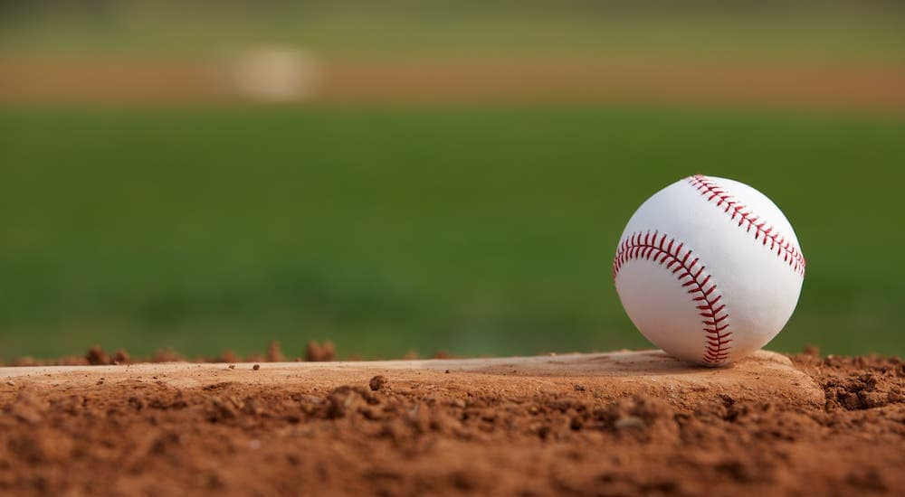 A closeup shows a baseball on a field.