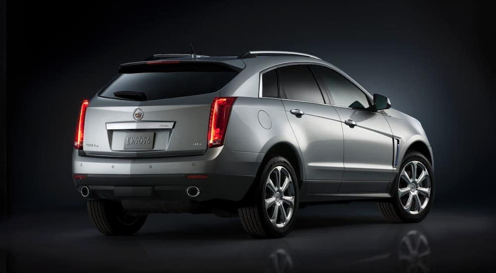 A rare used Cadillac SUV for sale around Fort Worth, a silver 2016 Cadillac SRX, is shown from behind in a dark warehouse.