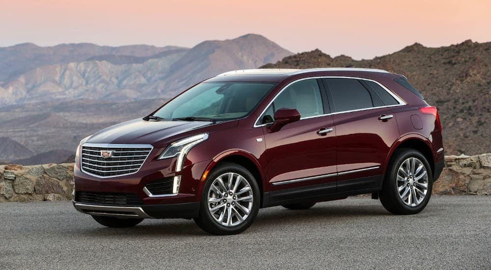A red 2018 Cadillac XT5 is parked in front of a canyon.