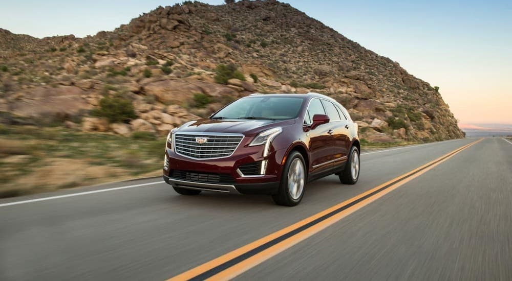 A classic used Cadillac for sale in Fort Worth, a red 2017 Cadillac XT5, is driving on a highway past a hill.