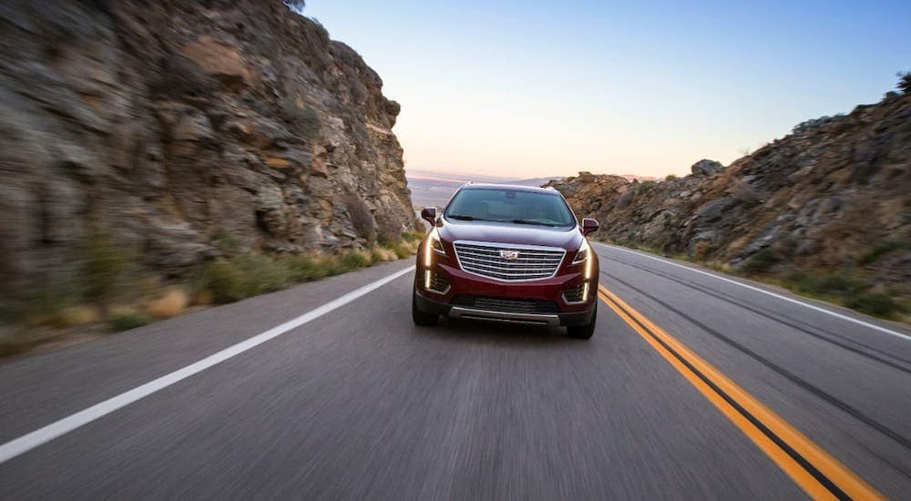 A red 2017 Cadillac XT5 is shown from the front driving on a highway near Fort Worth, TX.