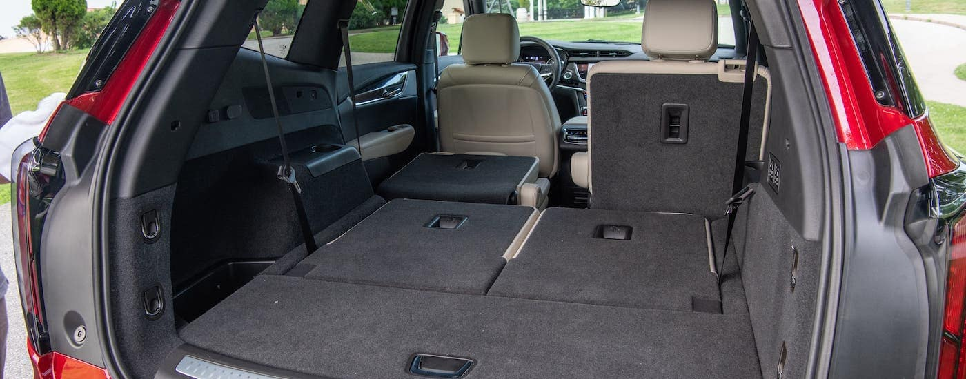 The cargo area is shown in a 2020 Cadillac XT6 with the rear seats folded down.
