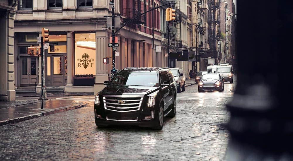 A black 2017 used Cadillac Escalade is driving on a cobblestone street in a city near Fort Worth, TX.