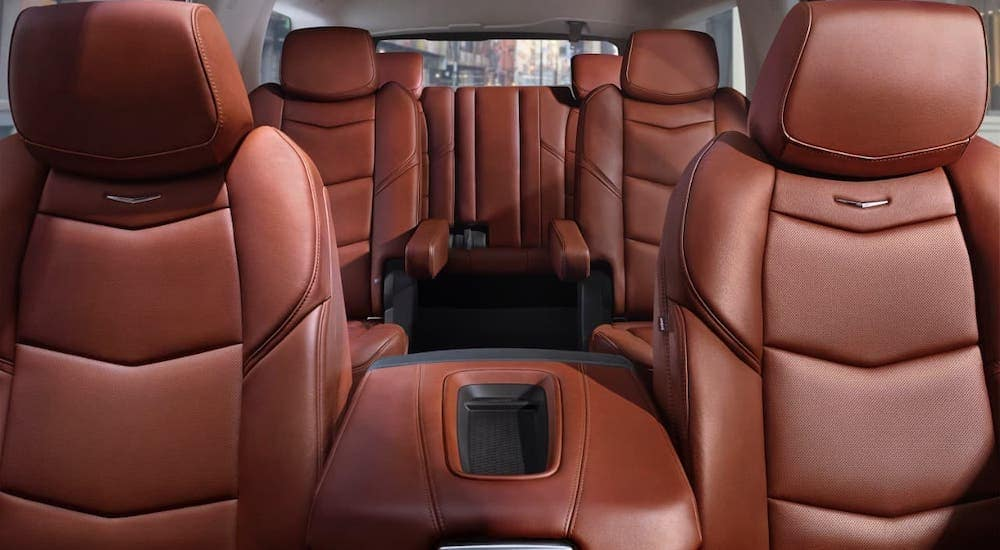 The brown leather interior is shown from the dashboard facing backwards in a 2018 Cadillac Escalade.