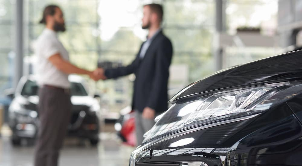 Two men are shaking hands at a dealership.