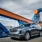 A blue 2019 used Cadillac XT4 is driving over a blue and orange bridge.