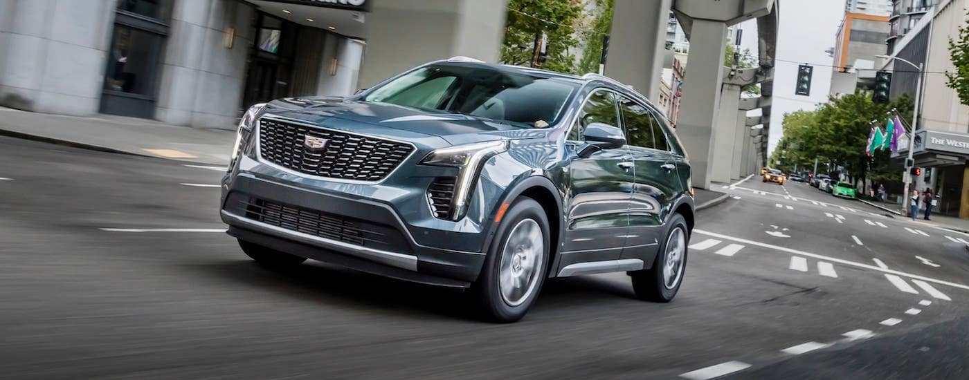 A gray 2019 Cadillac XT4 is driving on a city street.