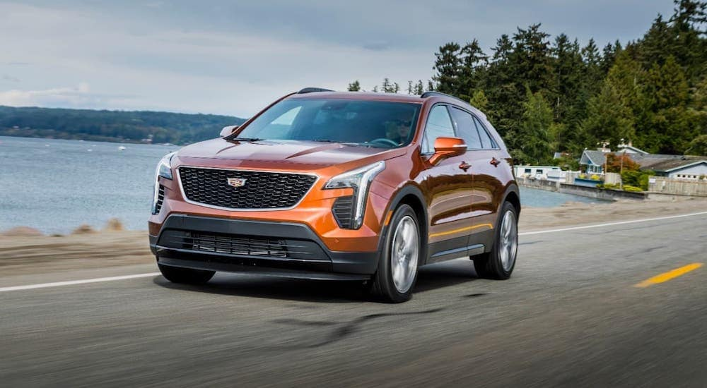 An orange 2019 used Cadillac XT4 is driving on a highway past a lake.