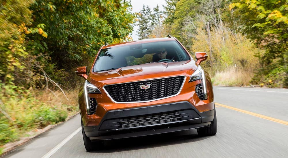 A orange 2020 Cadillac XT4 is shown from the front driving down the road.