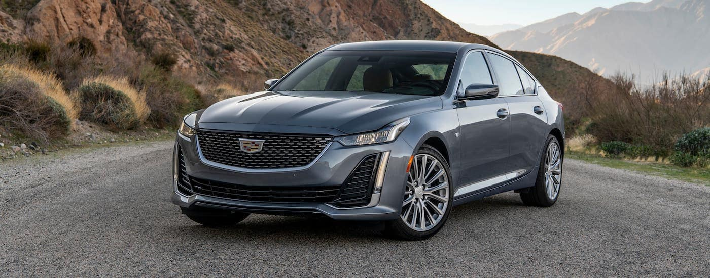 A gray 2020 Cadillac CT5 from a Cadillac dealer near you is parked on a gravel road in front of hills.