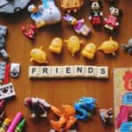 A Collection of Children's Toys and the Word 'Friends' Spelled Out with Scrabble Pieces