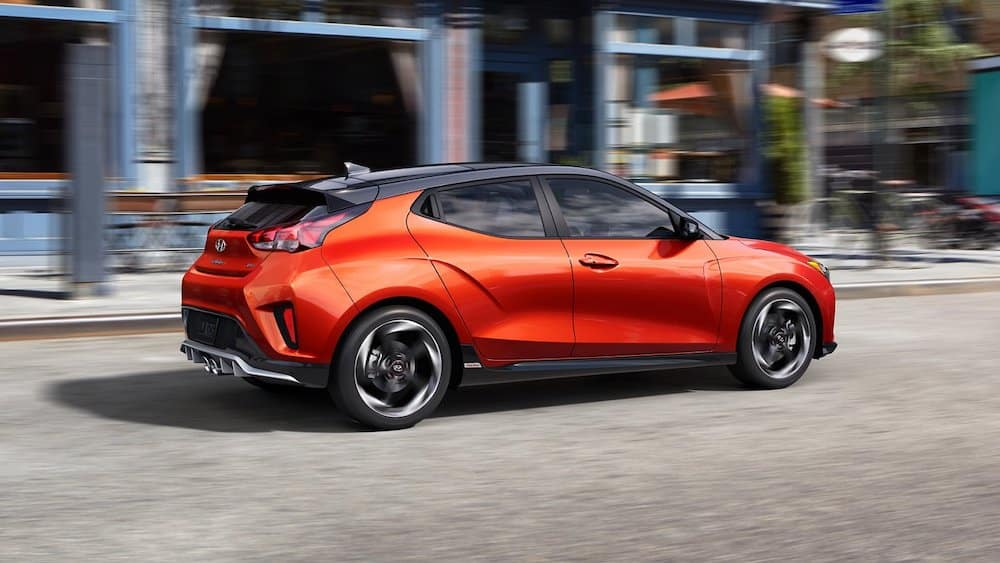2021 Hyundai Veloster driving down a city road.