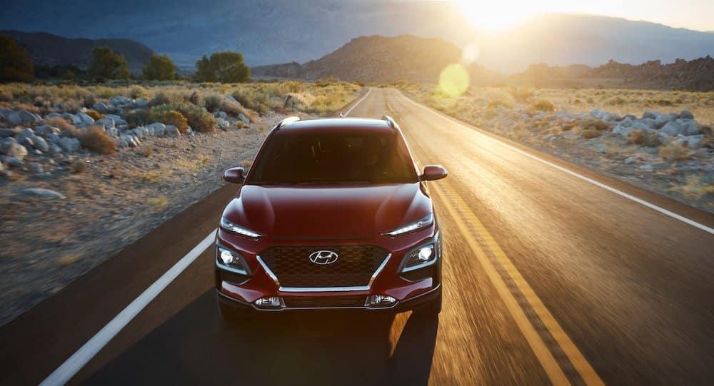 2021 Hyundai Kona driving down a road.