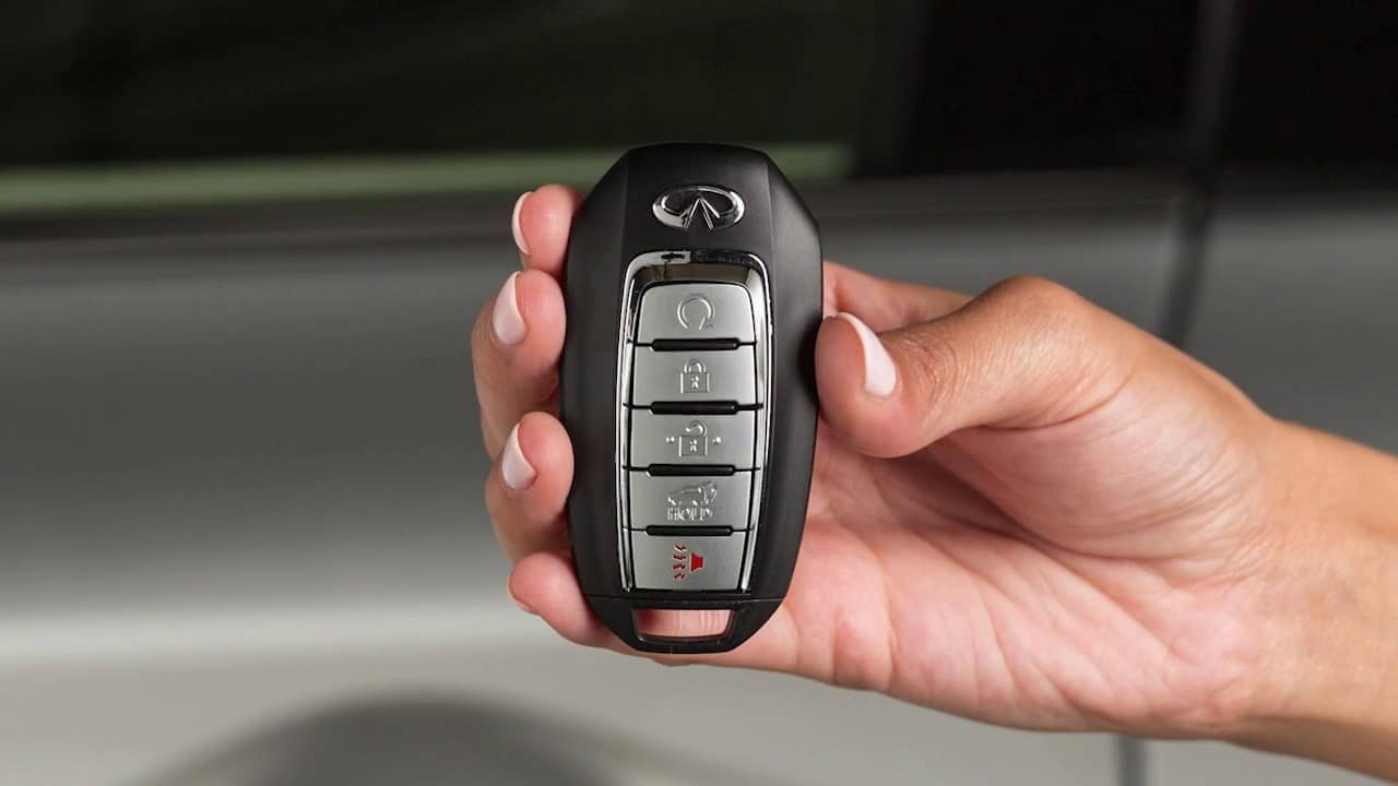 A person's hand holding an INFINITI key fob