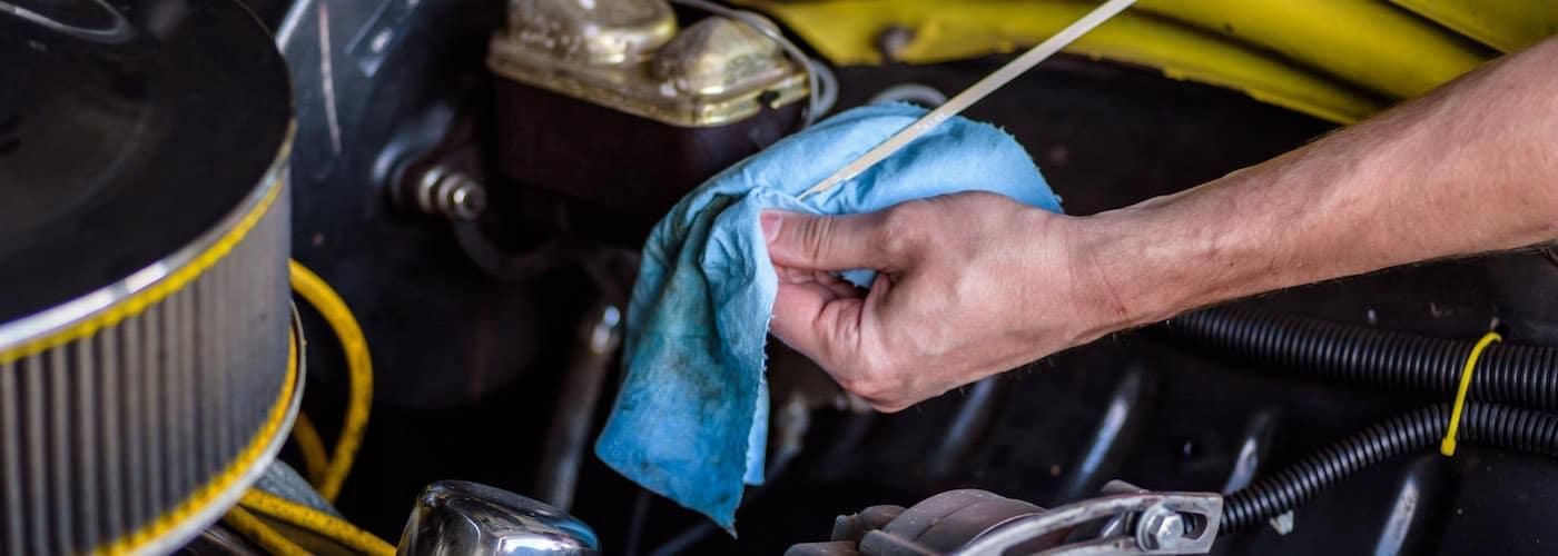 A car mechanic checking transmission fluid