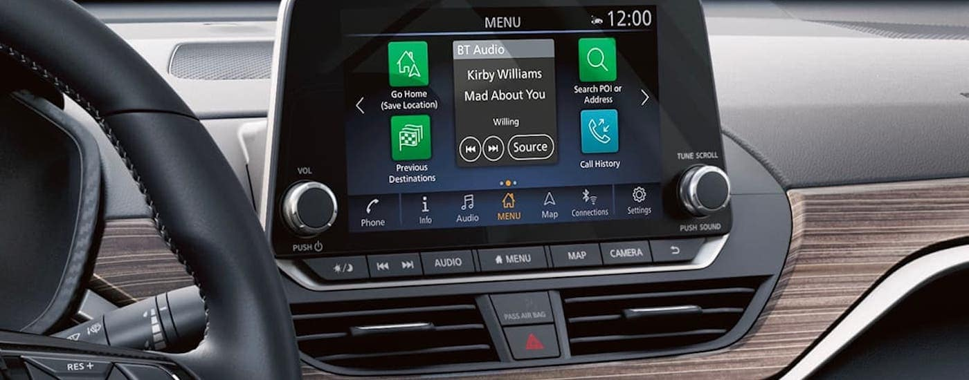 The infotainment screen and wood paneled dashboard is shown in a 2021 Nissan Altima.
